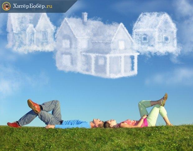 Люди на траве смотрят на облака в виде домов в небе