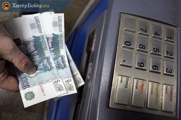 Рука с купюрами рядом с банкоматом