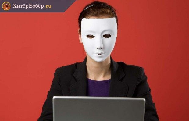 Женщина в маске перед монитором компьютера