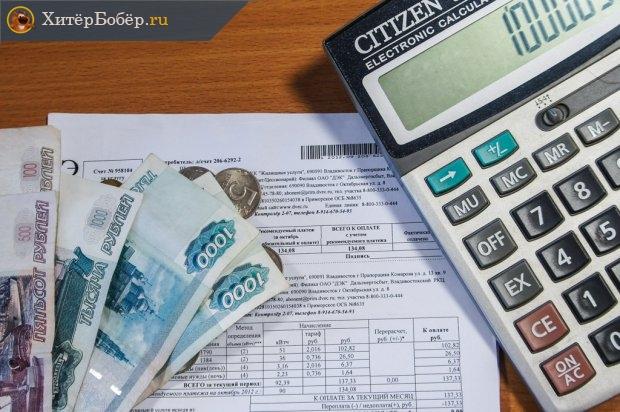 Квитанция за ЖКХ, денежные купюры и калькулятор на столе