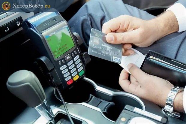 Онлайн-касса в автомобиля и мужчина с банковской картой в руках