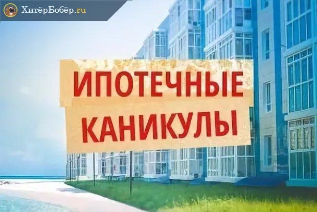 Надпись «Ипотечные каникулы» на фоне многоквартирного дома