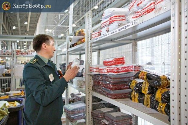 Таможенник осматривает товар на полках