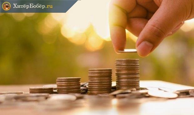 Рука выкладывает монеты в столбики
