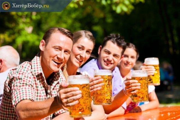 Люди пьют пиво за столом на улице
