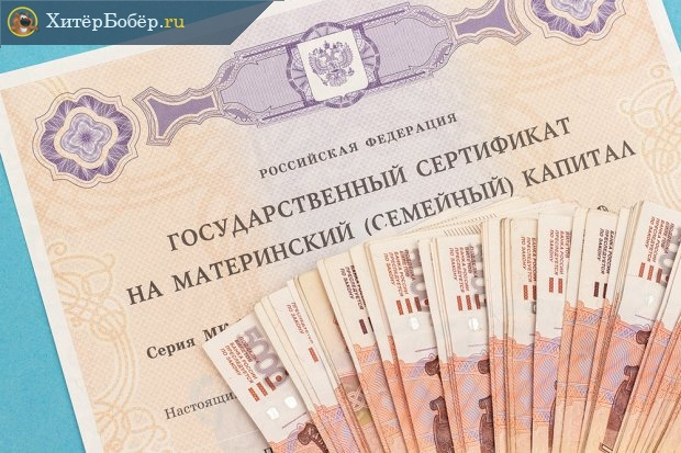 Пятитысячные купюры на фоне сертификата на материнский капитал