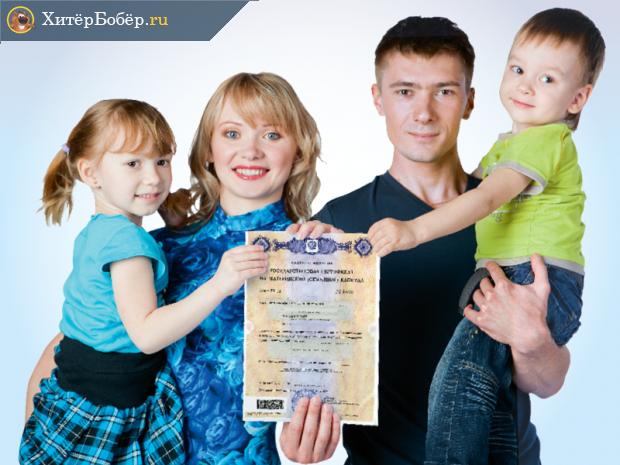 Родители и двое детей держат сертификат на материнский капитал