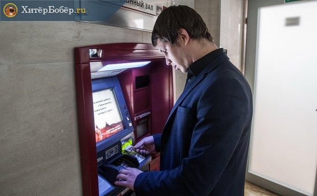 мужчина стоит у банкомата