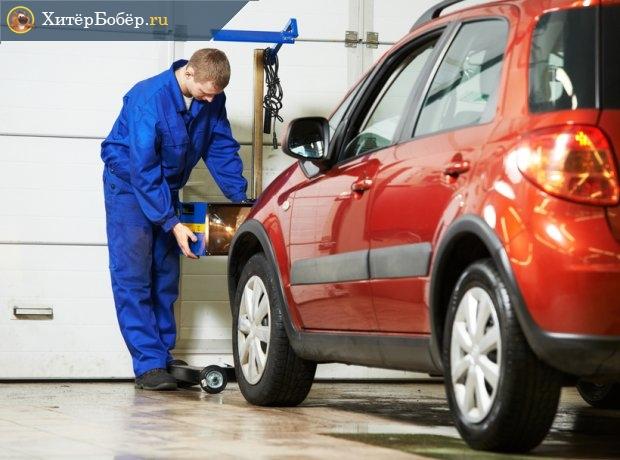 Специалист автосервиса осматривает автомобиль