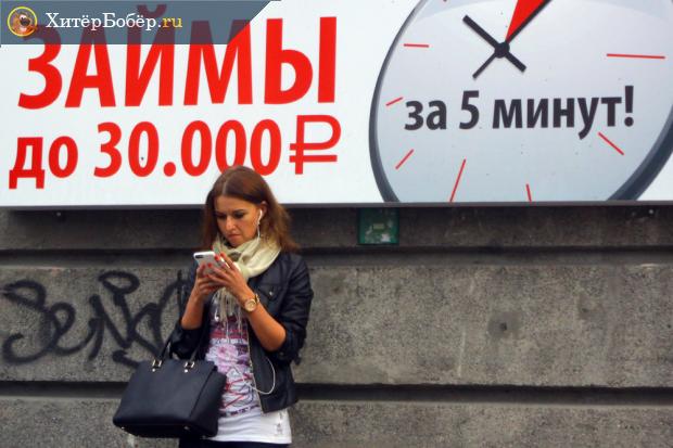 Женщина смотрит в телефон под плакатом с рекламой микрозаймов
