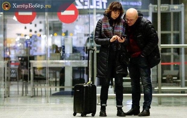 Мужчина и женщина с чемоданом на границе в аэропорту
