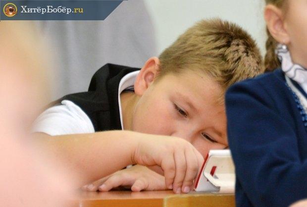 Школьник лежит на парте и смотрит в смартфон