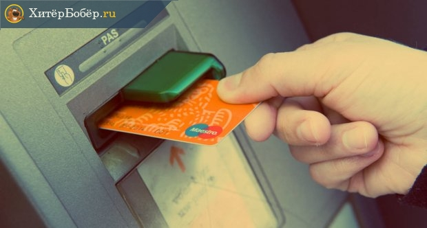 Рука вставляет карту в банкомат