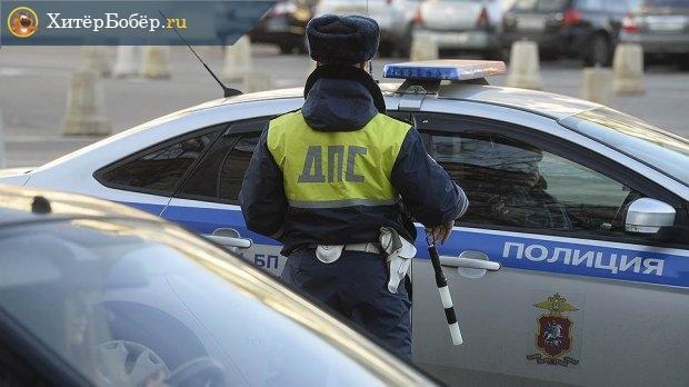 Инспектор ГИБДД на улице у патрульной машины