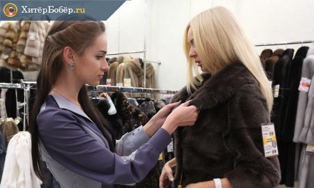 Продавец помогает женщине примерить шубу
