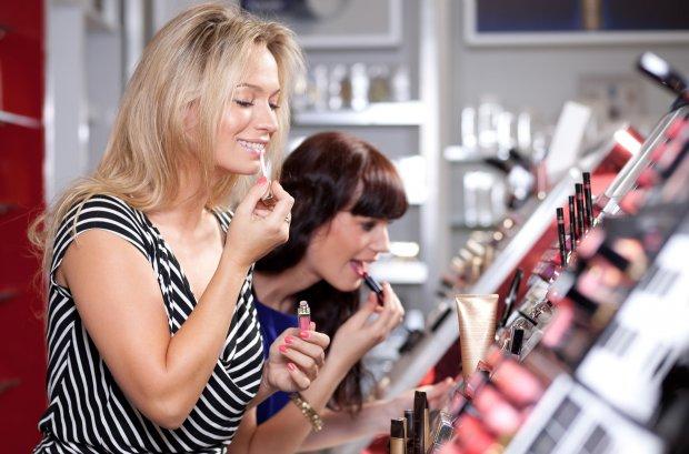 Женщины красятся у стенда с косметикой