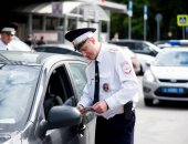 Сотрудник ГИБДД проверяет документы у водителя авто