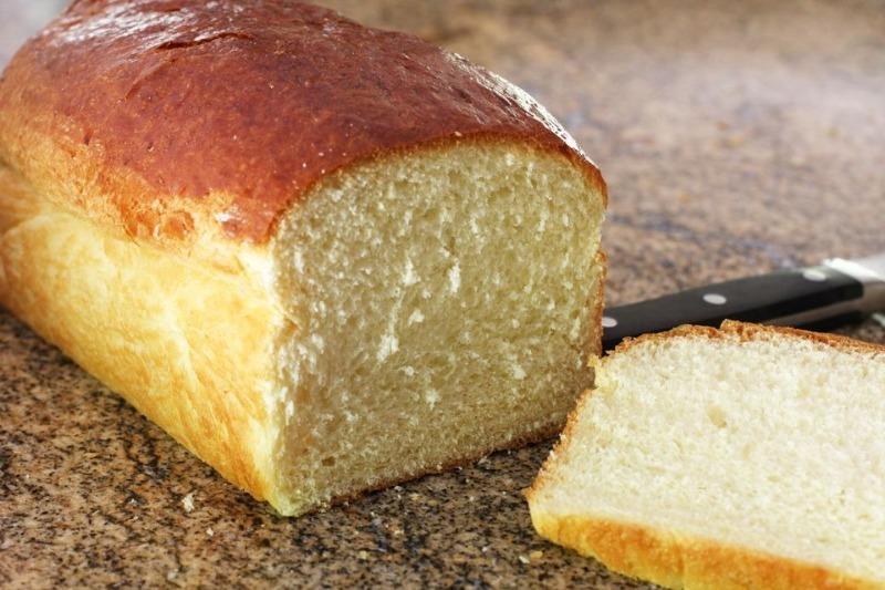 На столе отрезанный от буханки ломтик хлеба