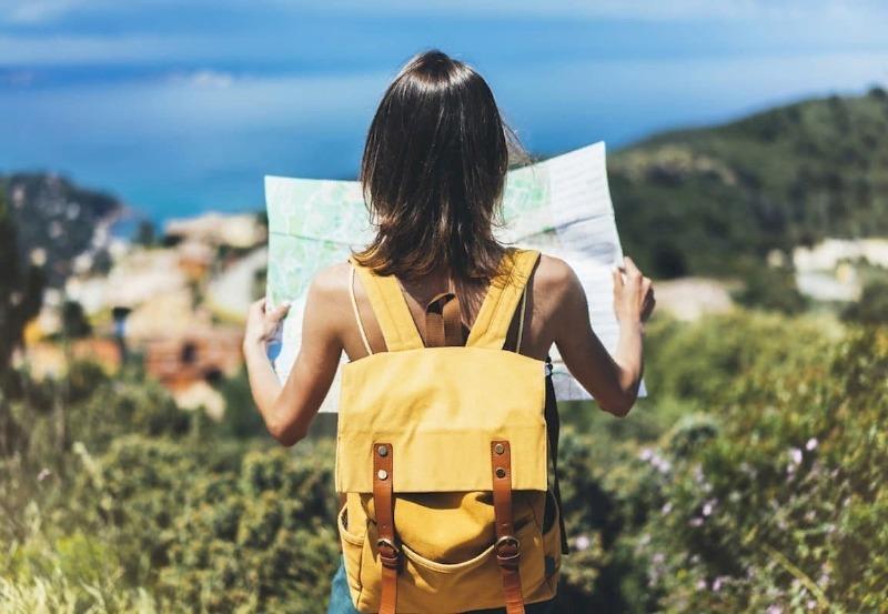 Девушка с желтым рюкзаком смотрит карту