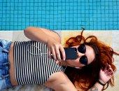 женщина с телефоном у бассейна